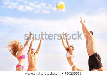 Woman in beachwear playing with beach ball Stock photo © stockyimages