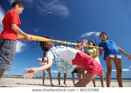 Teenagers doing limbo dance on beach Stock photo © monkey_business