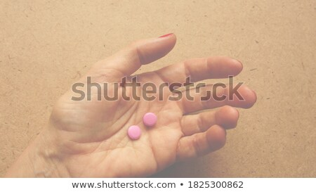 Closeup of woman hand holding two pills in her hand stock photo © jaycriss