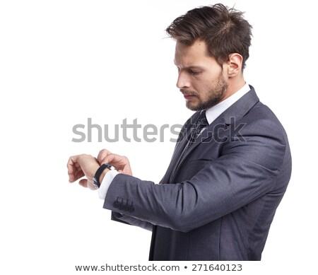 Jóképű üzletember néz óra fehér arc Stock fotó © deandrobot