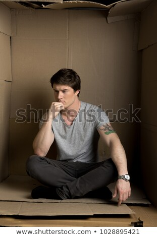 man sitting on a box and thinking while touching his chin Stock photo © feedough