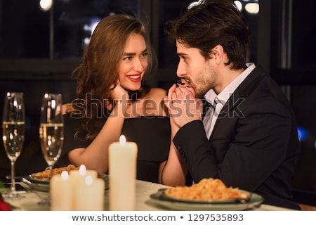happy elegant couple holding a bottle of champagne and glasses stock photo © feedough