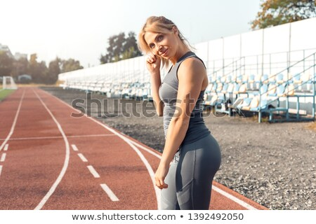 Cute playful young woman standing and looking back Stock photo © deandrobot