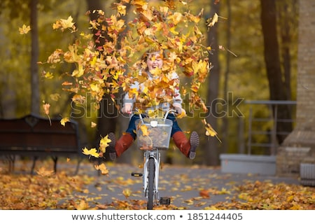 Trendy fashion woman riding bike on fall season Stock photo © cienpies