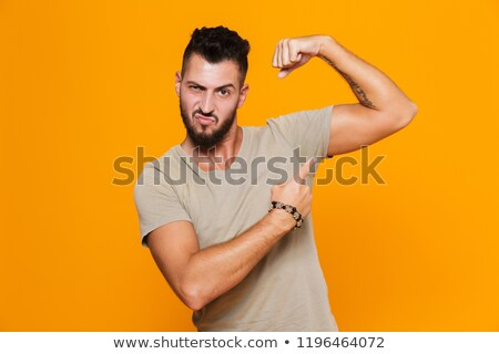 Young male showing biceps and fist Stock photo © zurijeta