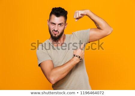 fiatal · férfi · mutat · bicepsz · ököl · kéz - stock fotó © zurijeta