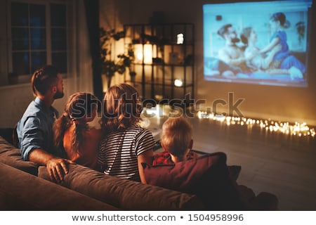 Man sitting in cinema watch film eating popcorn. Stock photo © deandrobot