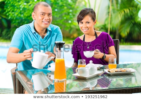 young indonesian couple having breakfast stock photo © kzenon