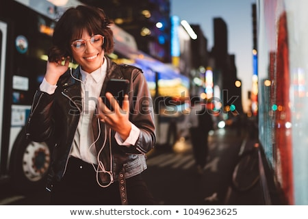 Cheerful young woman listening music with earphones. Stock photo © deandrobot