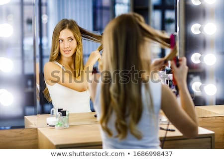 woman curling her hair stock photo © ssuaphoto