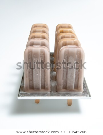 Coffee ice cream. Plastic molds with homemade ice cream on a stick on a white background with reflec Stock photo © artjazz