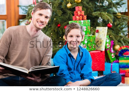 Foto d'archivio: Daddy Reading Out From Book For Kid Under X Mas Tree