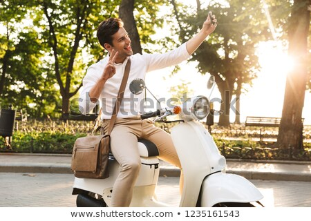 young business man walking outdoors on scooter take a selfie by mobile phone stock photo © deandrobot