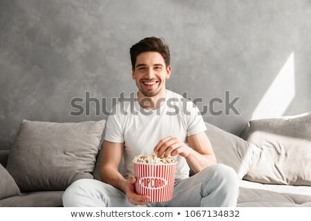 Cheerful bachelor sitting on sofa in gray apartment and laughing Stock photo © deandrobot