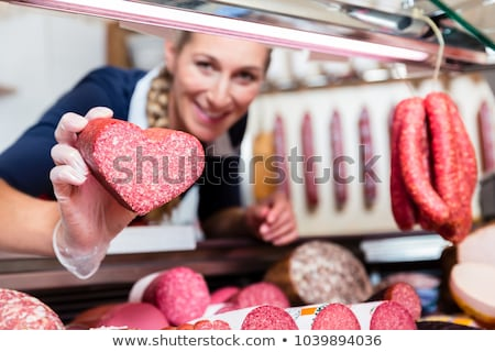 Sales woman in meat shop showing a heart shaped sausage Stock photo © Kzenon