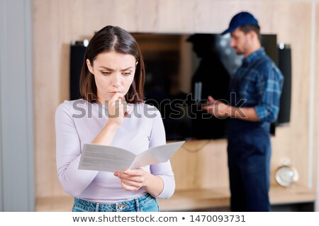 Young perplexed woman reading leaflet with usage instructions Stock photo © pressmaster