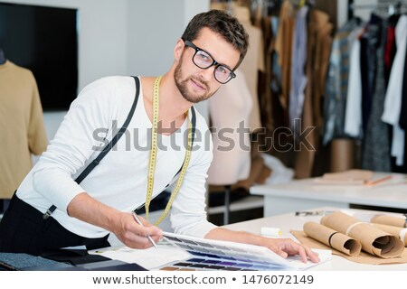 Young professional fashion designer with measuring tape looking at you Stock photo © pressmaster