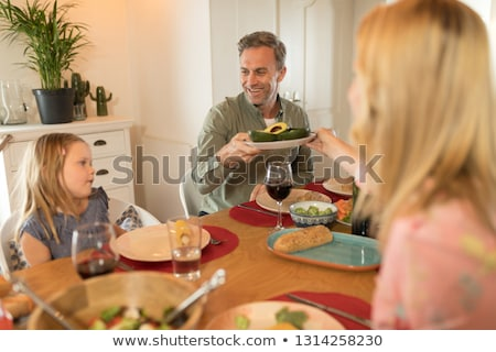 rear view of a woman passing food to man on dining table at home Stock photo © wavebreak_media