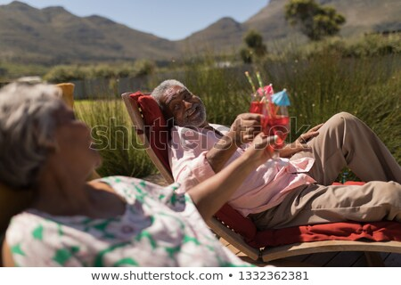 side view of african american senior couple toasting glasses of orange juice while sitting at the d stock photo © wavebreak_media