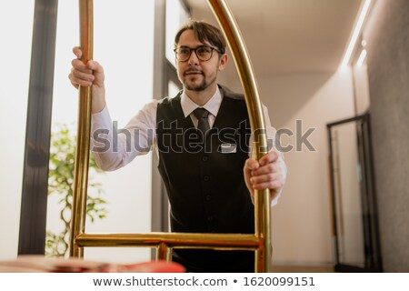 Well-dressed bearded porter in eyeglasses pushing cart with baggage Stock photo © pressmaster