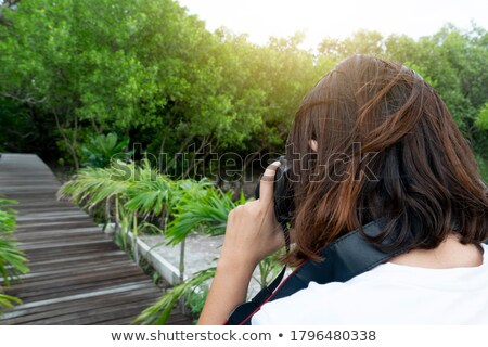 Young woman taking a picture in a wooded area Stock photo © wavebreak_media