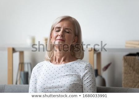 Peaceful blonde meditating with eyes closed Stock photo © wavebreak_media