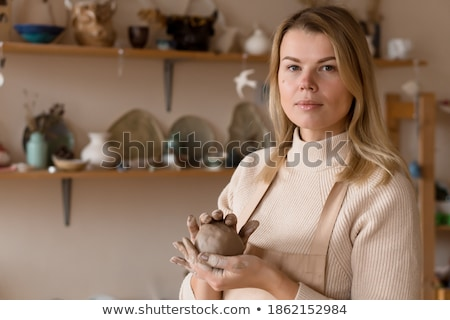 Clay piece holded by hands of woman potter in apron Stock photo © deandrobot
