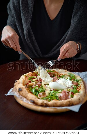 fresh pizza on a wooden plate in female hands. Selective focus. Stock photo © Yatsenko