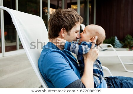 Father with baby son sitting on lounge chair Stock photo © IS2