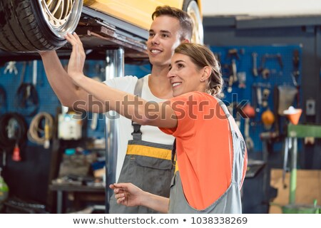 two dedicated auto mechanics checking the modified wheels of a tuned car stock photo © kzenon