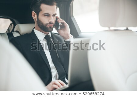 Handsome young businessman working with laptop while sitting on  stock photo © Freedomz