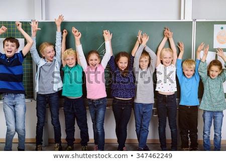 School kids standing in row and raising hand in classroom of elementary school Stock photo © wavebreak_media