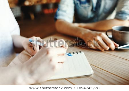 Student or businesswoman with notebook and pen making notes in front of laptop Stock photo © pressmaster