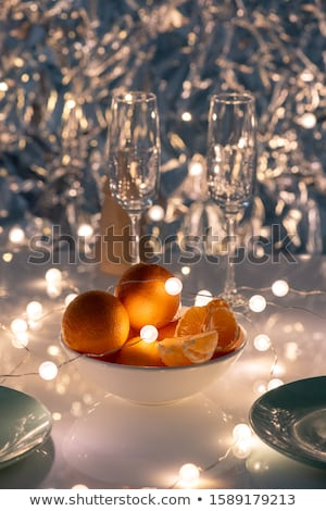 White porcelain bowl of oranges with garlands and two flutes on table Stock photo © pressmaster