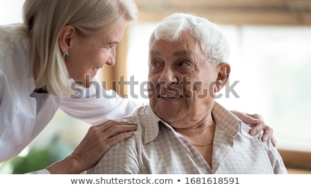 Attentive female doctor explains diagnosis to patient, gives professional consultancy, points with p Stock photo © vkstudio