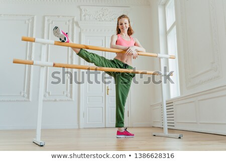 Female model has aerobics class, stretches legs on ballet barre, wears sportshoes and sportswear, le Stock photo © vkstudio