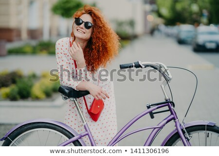 People, leisure, lifestyle and spare time concept. Cheerful curly woman focused into distance, rides Stock photo © vkstudio