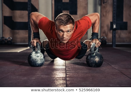 Young Men Lifting Kettle Bell In Gym Stock photo © Jasminko