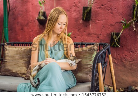 A young woman having a mediterranean breakfast seated at her sofa and with her cat Stock photo © galitskaya