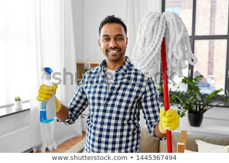 smiling indian man with detergent cleaning at home Stock photo © dolgachov