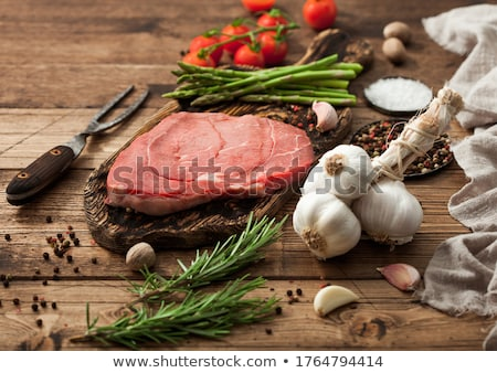 Slice of fresh raw barbeque braising beef steak on chopping board with asparagus and garlic with tom Stock photo © DenisMArt
