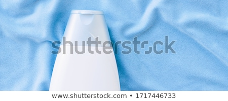 Blank label shampoo bottle or shower gel mockup on blue silk background, beauty product and body car Stock photo © Anneleven
