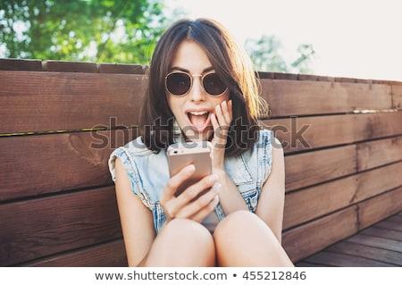 boldog · meglepődött · lány · néz · mobiltelefon · telefon - stock fotó © dacasdo