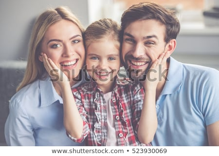 Cheerful family of three facing camera and smiling Stock photo © stockyimages