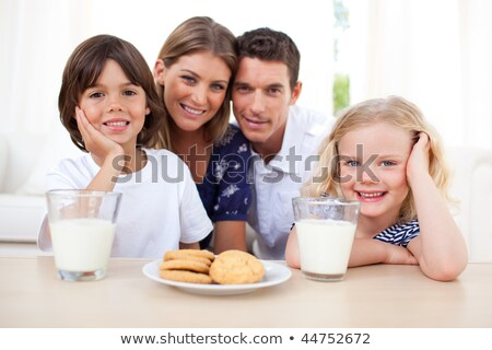 Happy brother and sister eating biscuits and drinking milk  Stock photo © wavebreak_media