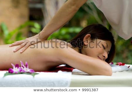 Asian woman having a massage in tropical setting Stock photo © Kzenon