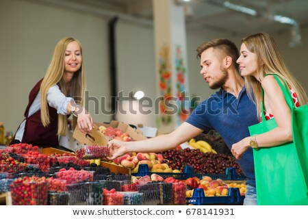 Smiling Young Man And Woman Buy Peaches In Supermarket Stock fotó © O_Lypa