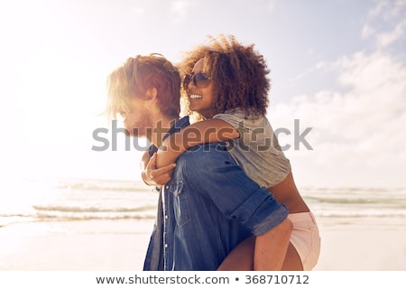 beautiful young couple standing and laughing on the beach stock photo © deandrobot