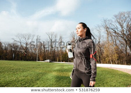 Woman pretty runner looking aside in autumn park Stock photo © deandrobot