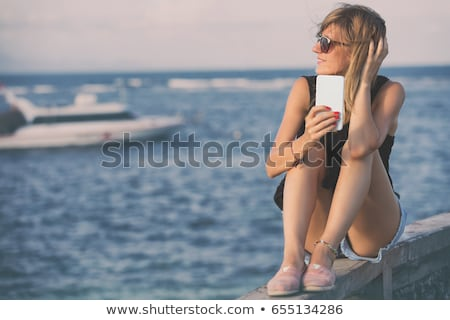 Female tourist using mobile phone at seaside on summer holiday Stock photo © stevanovicigor